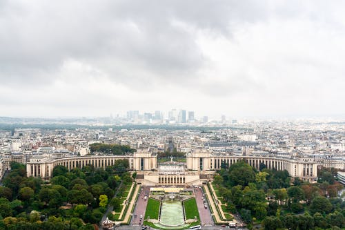 Amazing aerial view of aged Palais de Chaillot and fountain located in Trocadero Gardens with lush green trees against overcast sky in Paris