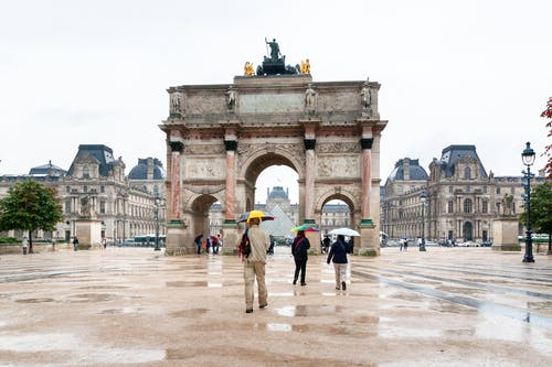 Unrecognizable travelers with umbrellas walking near triumphal arch on rainy day
