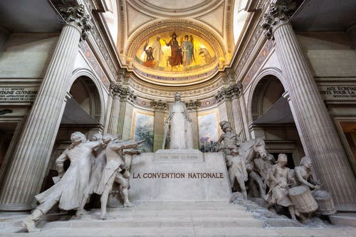 From below of huge illuminated statue of marble devoted to La Convention Nationale located in archway near museum