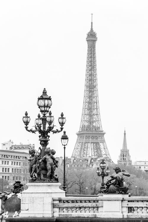 Eiffel tower near heavy sculptures and vintage streetlights