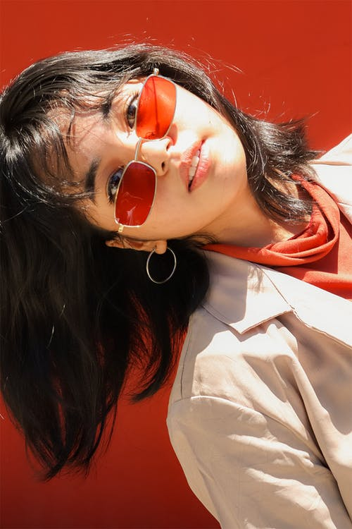 Woman in White Shirt Wearing Red Sunglasses