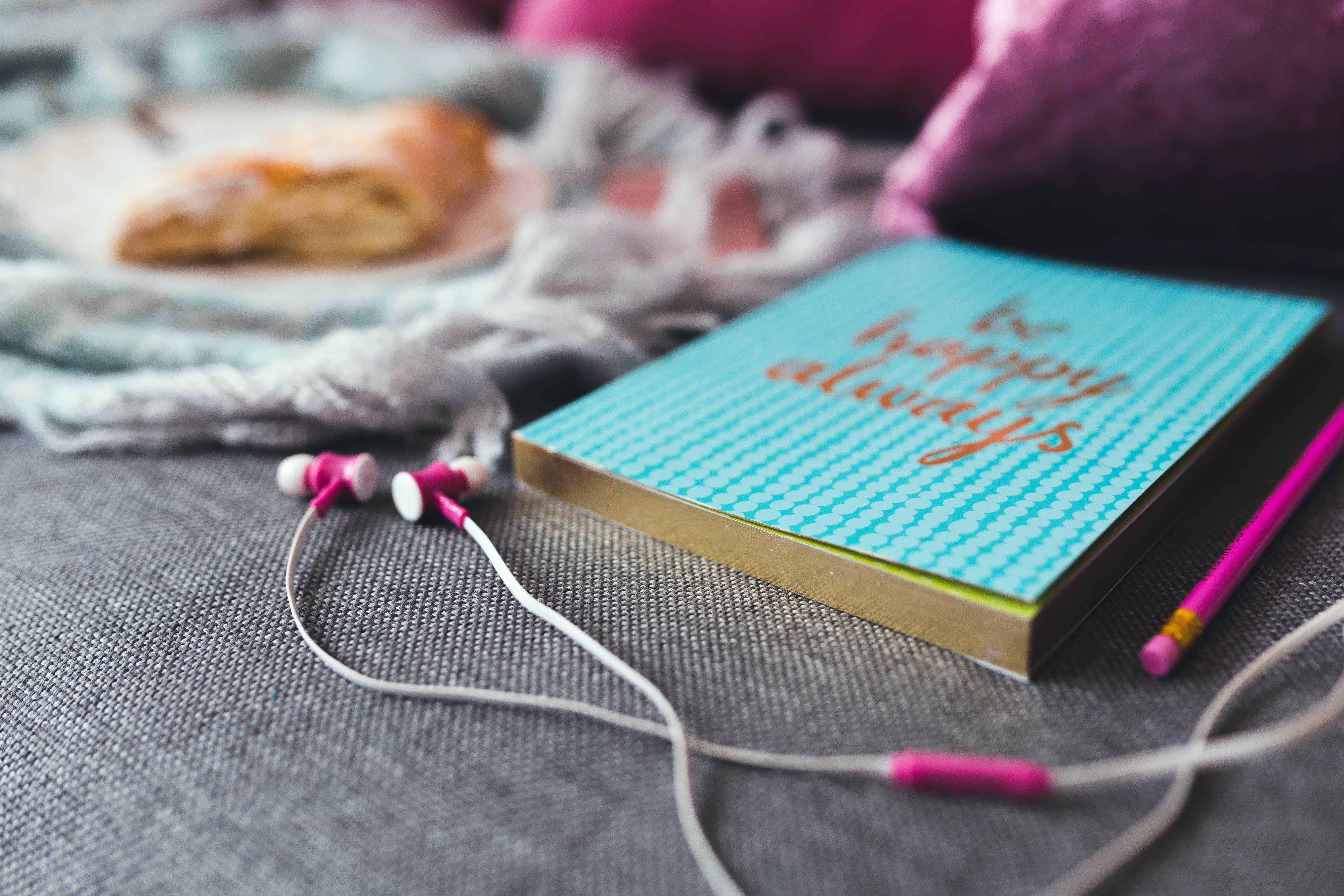 White and Pink Earphones on Gray Textile