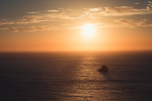 Picturesque view of shiny sun in cloudy sky over endless ocean with rock at sunset