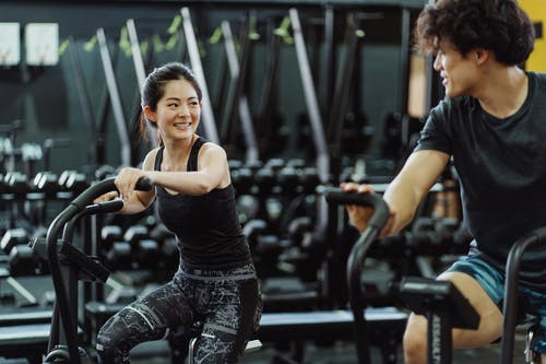 A Couple Using Elliptical Trainers