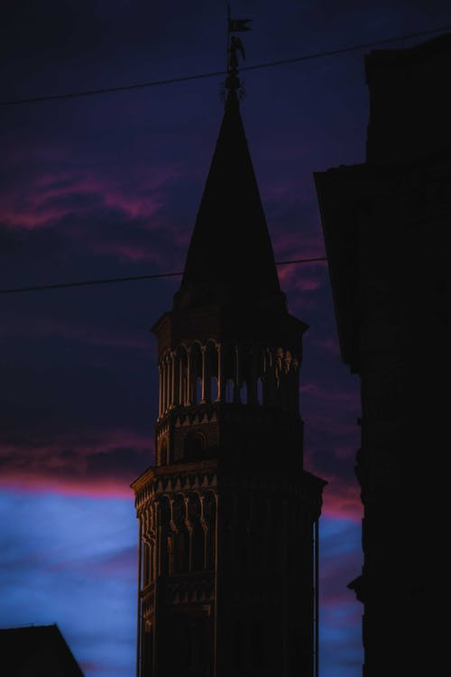 Facade of ancient cathedral tower decorated with pillars and spire at dark night