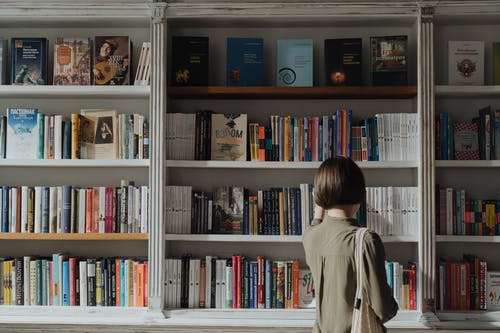Woman in Beige Long Sleeve Shirt Standing in Front of White Wooden Book Shelf