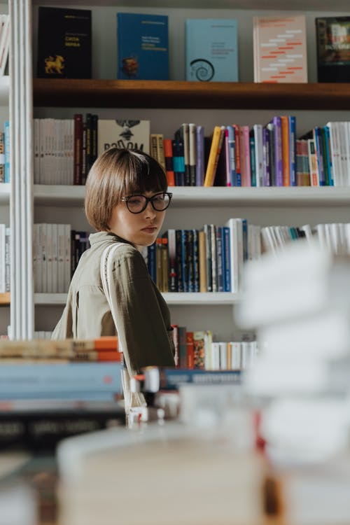 Woman in Gray Long Sleeve Shirt Standing in Front of Books