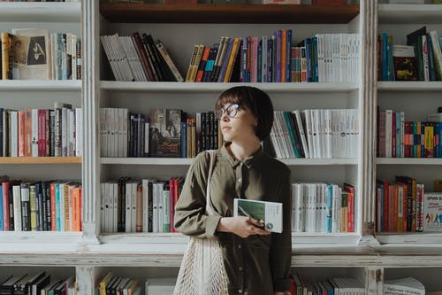 Woman in Green Coat Holding Book