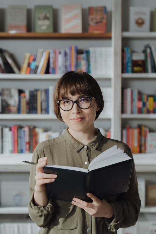 Woman in Green Button Up Shirt Wearing Black Framed Eyeglasses Reading Book