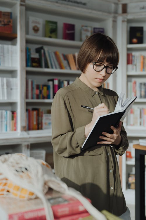 Woman in Brown Coat Holding Book