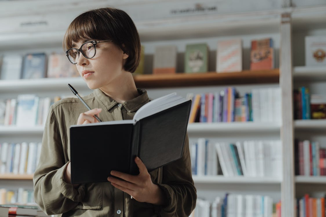 Woman in Green Jacket Reading Book