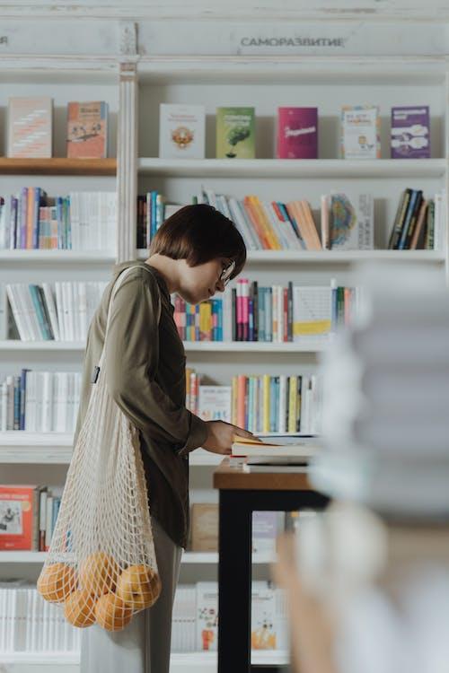 站在書架前的灰色長袖連衣裙的女人