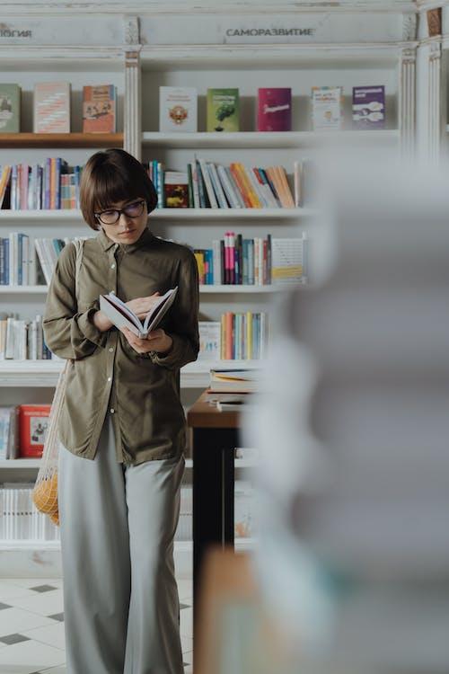 棕色外套拿著本書的女人