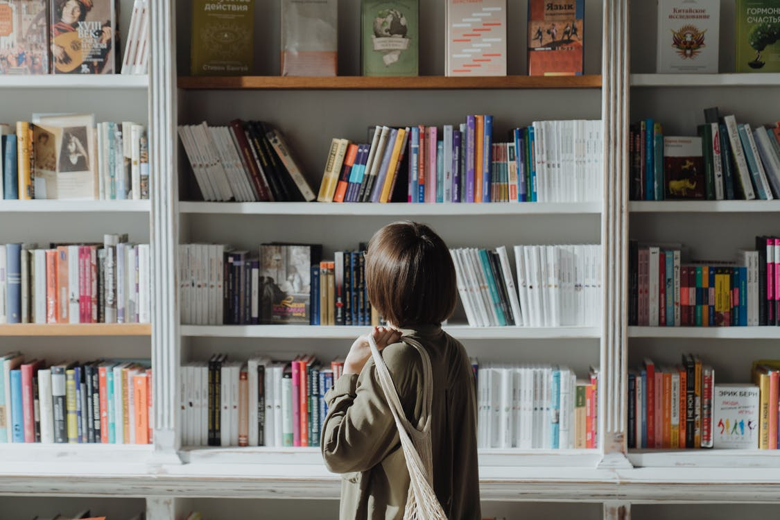 Woman in Beige Coat Standing Near White Wooden Book Shelf
