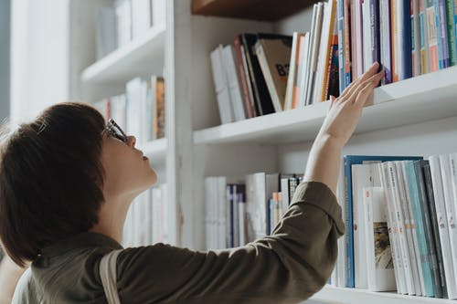 Woman in Brown Long Sleeve Shirt Wearing Black Framed Eyeglasses