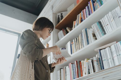 Woman in Gray Coat Reading Books