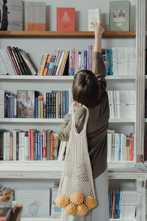 Woman in Beige Long Sleeve Dress Standing in Front of White Wooden Book Shelf