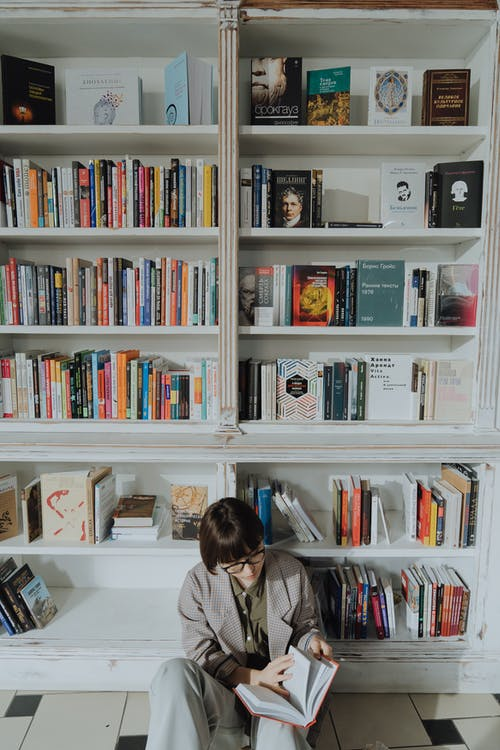 Woman in White Shirt Sitting Beside White Wooden Book Shelf