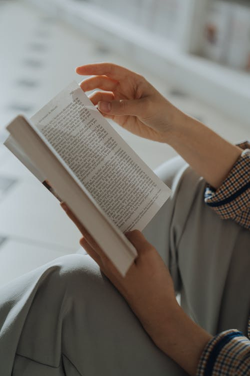 Person in White Long Sleeve Shirt Reading Book