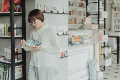 Woman in White Robe Holding White and Blue Book