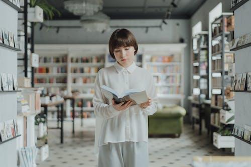 Woman in White Long Sleeve Dress Standing on White Floor Tiles