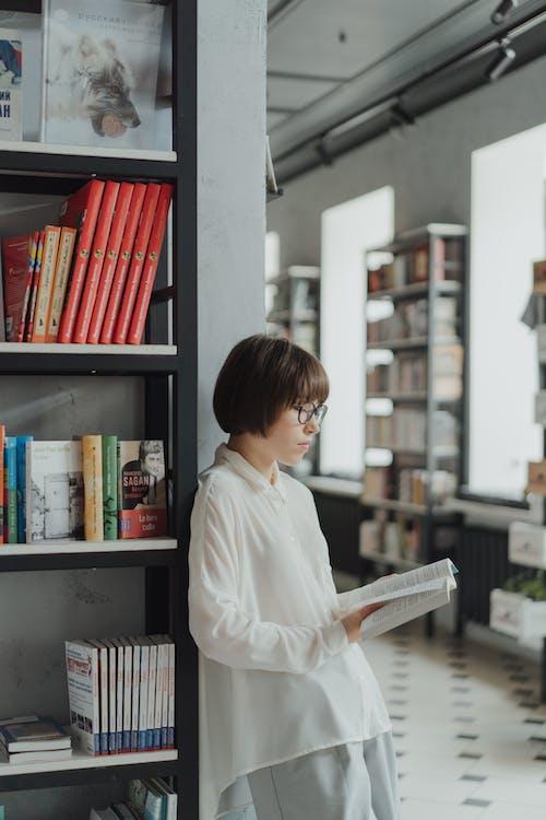Boy in White Dress Shirt Standing Beside Books