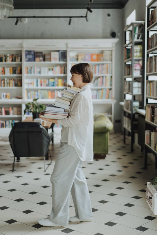 Woman in White Long Sleeve Dress Holding Book