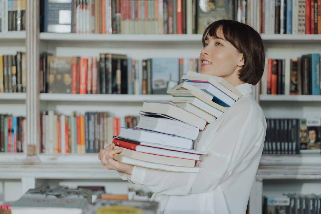 白色長袖襯衫閱讀書中的女人