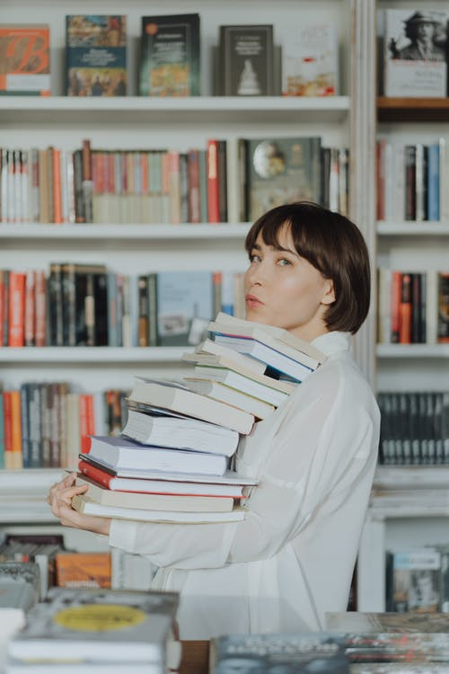 Woman in White Long Sleeve Shirt Standing Near Books