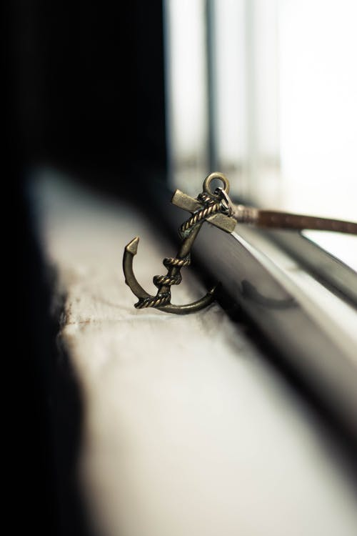 Soft focus of metal stylish charm in anchor shape with leather strap placed on grunge windowsill