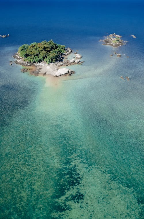Tropical islet in azure shallow sea