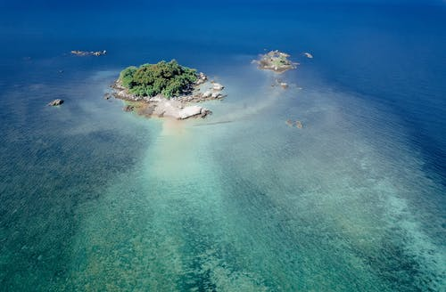 Drone view of turquoise shallow sea with small cay covered with lush tropical greenery in sunlight
