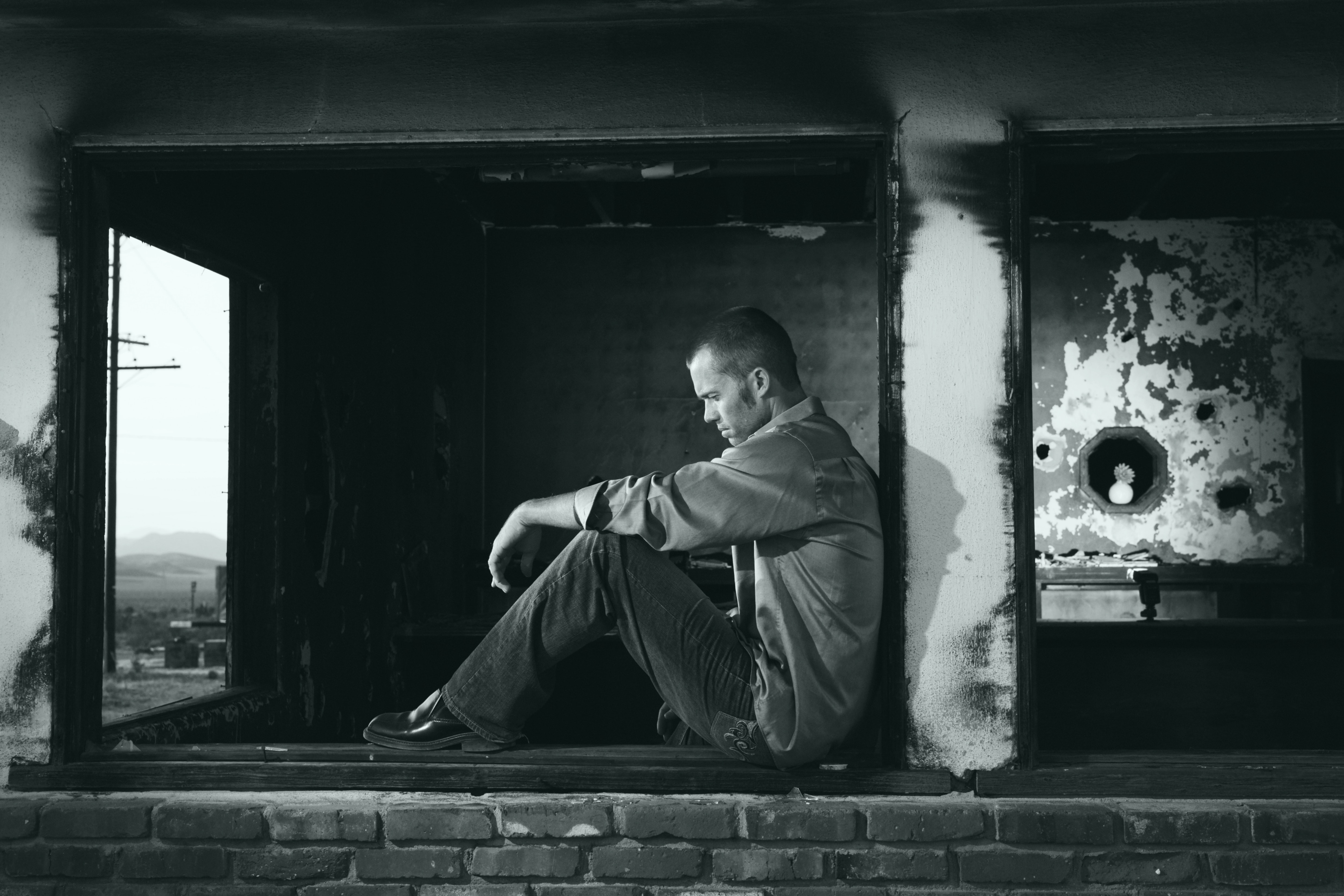 Grayscale photo of man sitting download a pic donate a buck