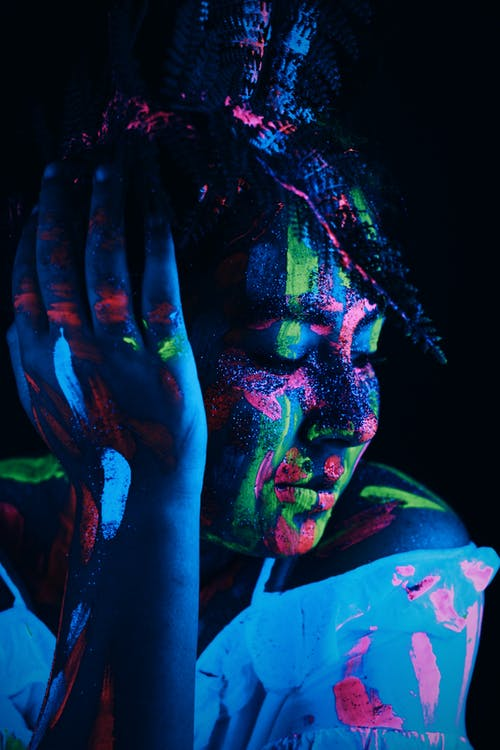 Creative woman with bright neon paints and shimmer on body