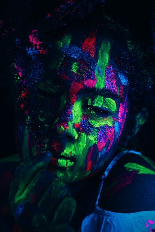 Woman covered with colorful neon paints shining on face under ultraviolet light in dark studio