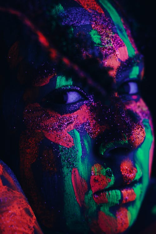 Crop female with shimmer and colorful neon paints on face glowing under ultraviolet light