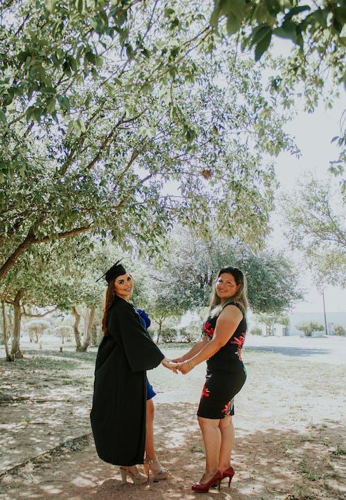 Women holding hands in park