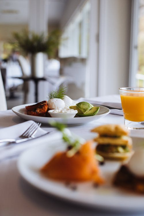 Fresh avocado slices with poached eggs and cheese sauce on plate near glass of refreshing beverage for brunch