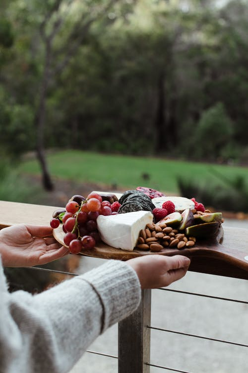 Crop anonymous female in sweater holding delicious cheese platter served with ripe juicy grapes and almonds while standing on veranda against blurred summer forest