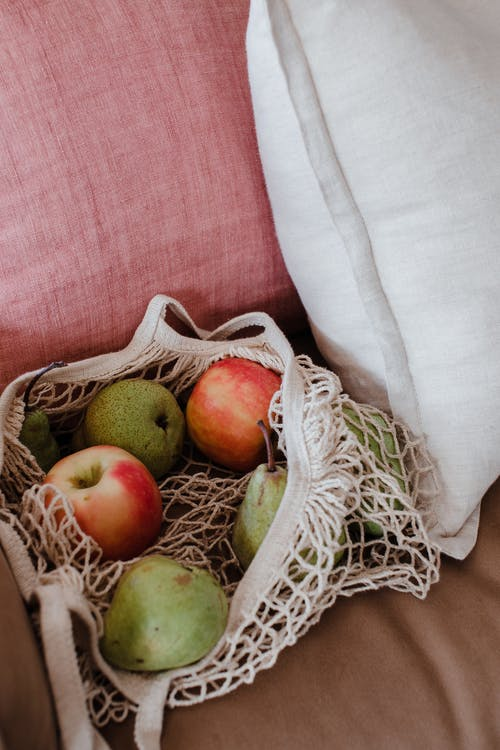 High angle net shopper bag with tasty green and red apples placed on pink comfy couch