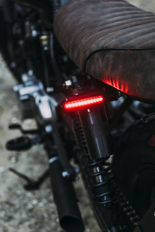 Closeup of modern motorcycle with red taillight and soft saddle parked on road