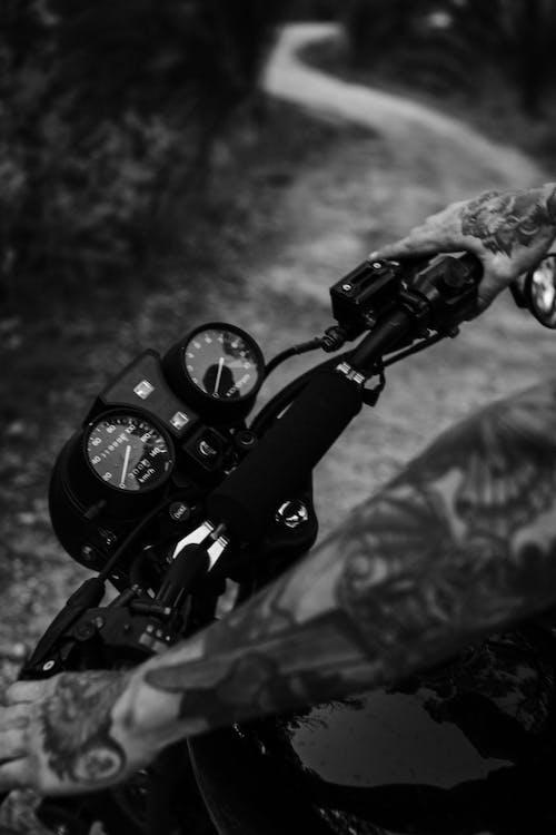 Crop tattooed biker on motorbike