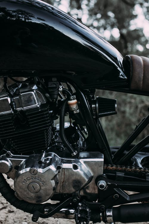 Closeup of modern shiny black metal motorcycle with soft saddle and big fuel tank on blurred background