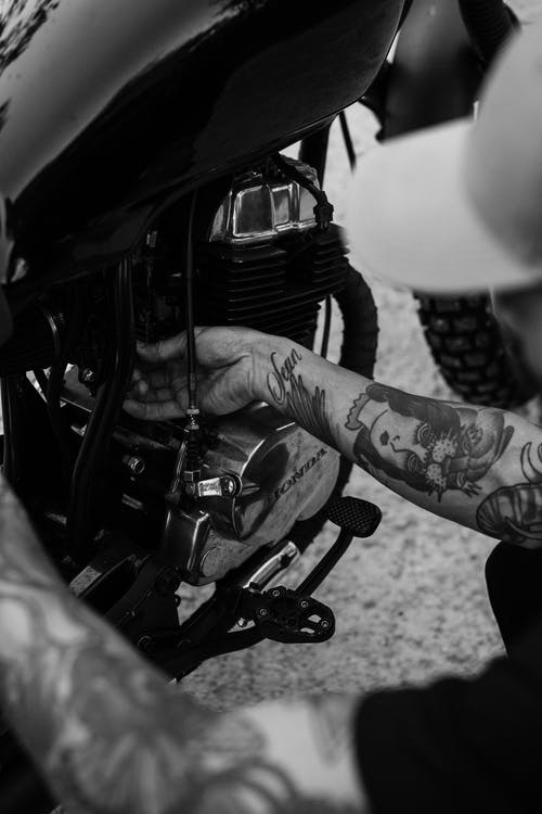 Black and white from above of crop unrecognizable tattooed male biker checking engine of motorcycle before riding