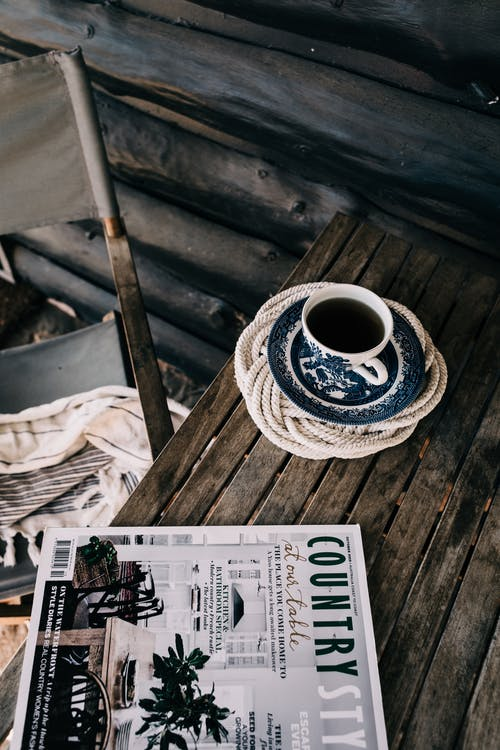 From above of wooden table with cup of hot aromatic drink on saucer placed near magazine