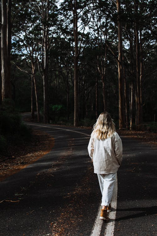Woman walking along road between trees
