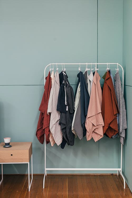 Collection of stylish cape coats hanging on metal rack near small wooden table in modern fashion store