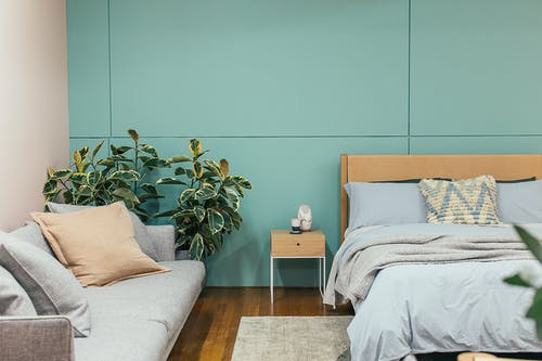 Cozy bedroom with minimalist furniture and blue and gray walls