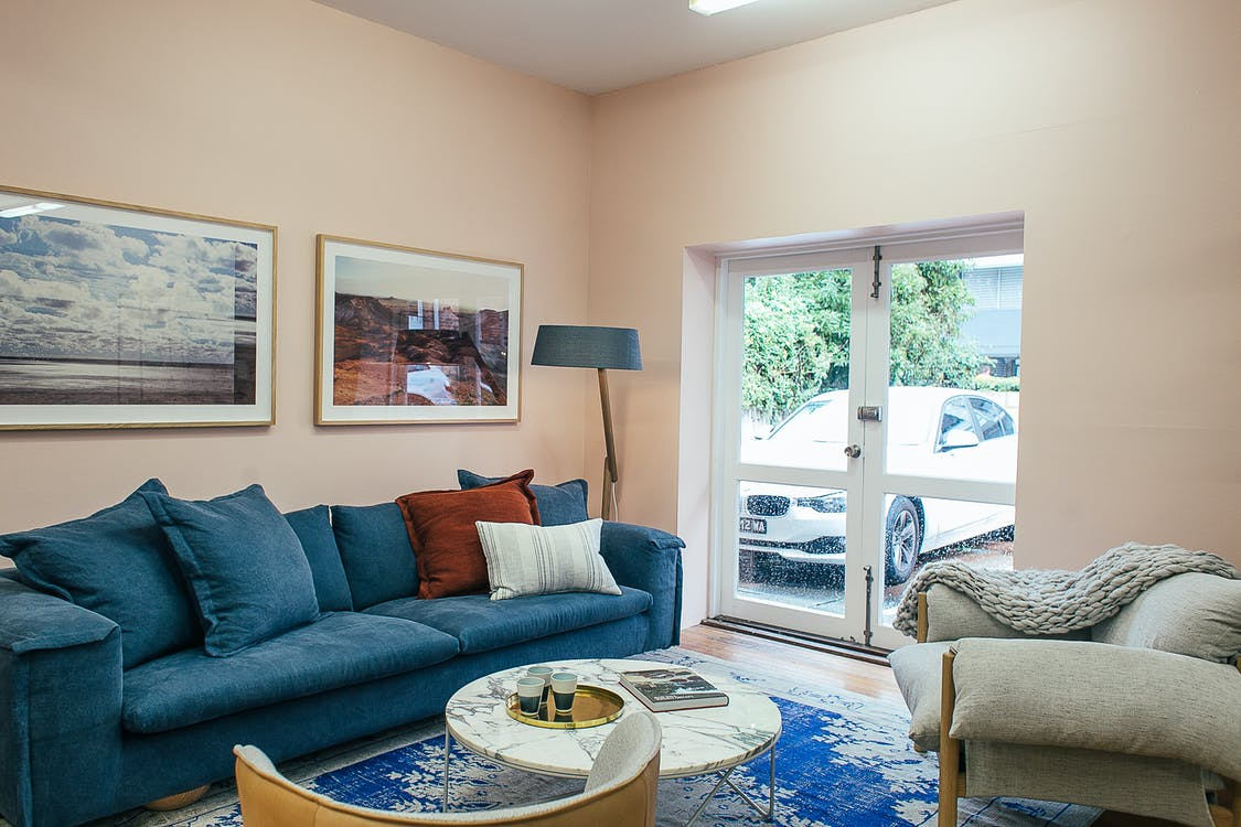 Comfortable sofa and armchair placed near small round marble table in cozy living room decorated with framed pictures and floor lamp