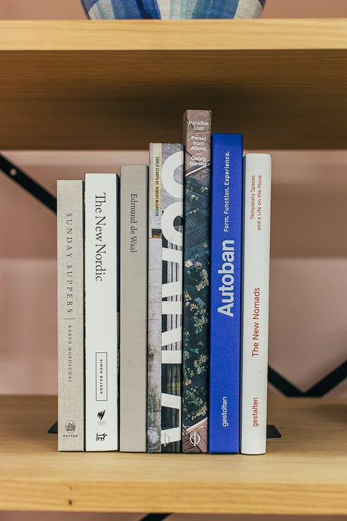 Stack of books placed on wooden shelf